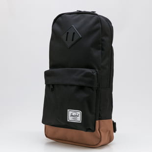 The Herschel Supply CO. A backpack from The Herschel Supply CO. in a black colorway with a front pocket and a brown bottom.- backpack- adjustable strap- zipper pocke